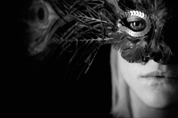A woman in a mask with a meloncoly expression in B&W.